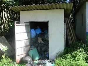 Grande lixeira na rua já está transbordando de lixo não recolhido há várias semanas.