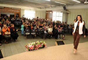 primeira-dama Lúcia França no palco, com diversas primeiras-damas e empresárias ao fundo em reunião do fundo social de solidariedade