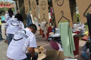 colaboradores da Fundação Alphaville montam araras de roupas durante a The Street Store