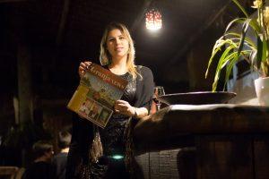 Paula Farias, proprietária do Tantra, segura um exemplar do jornal Granja News durante lançamento do livro Tributo a Elas