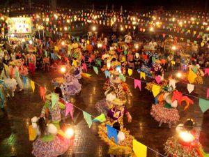 imagem de uma festa junina com bandeirinhas e várias pessoas dançando quadrilha