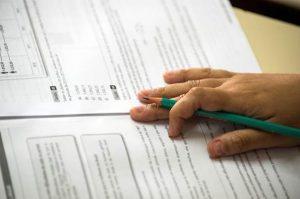 mão de um ou uma estudante sobre o caderno de questões do vestibular da Fatec