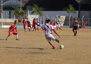jogadores do Bola Branca (de branco) e do Rubro Negro (de vermelho) disputam partida de futebol