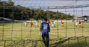 um goleiro visto de costas e através da rede do fundo do gol enquanto uma partida de futebol acontece mais ao fundo