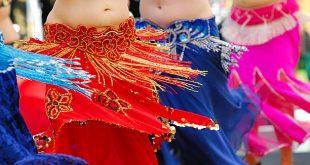detalhe da cintura e das barrigas de quatro mulheres fazendo dança do ventre
