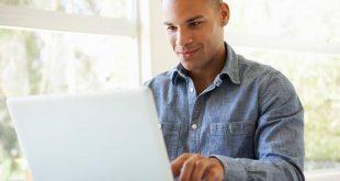 um homem sorri enquanto digita em um notebook branco
