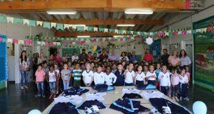 alunos posam para foto atrás de mesa com kits de uniformes escolares novos