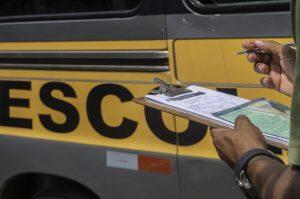 close das mãos de um funcionário da Settrans vistoriando uma vã escolar com uma prancheta