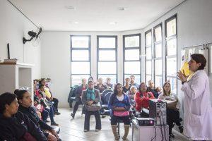 palestrante fala a um grupo de dezenas de participantes