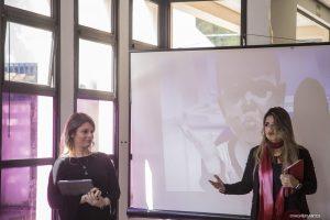 duas palestrantes falam com uma tela ao fundo