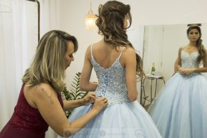 Maria Luiza ajeitando vestido azul de uma debutante