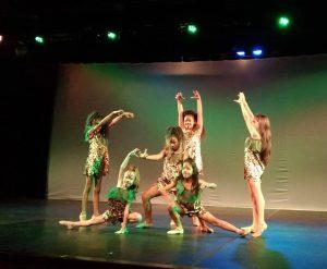 cena de espetáculo de teatro em Carapicuíba, com sete garotas se apresentando