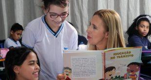 uma professora conversa com duas alunas segurando um livro com o título 'Educação no Trânsito'