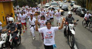 atletas correm com o fogo simbólico em mãos