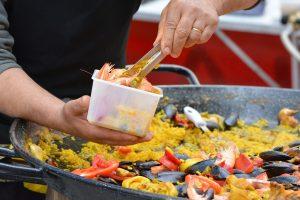 uma pequena porção de paella sendo colocada em um pote, com a grande panela de paella vista logo atrás