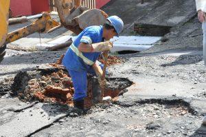 homem trabalhando em cratera em rua