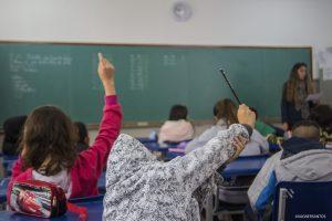 alunos vistos de costas e levantando suas mãos para tirarem dúvidas em sala de aula da Escola Municipal Edith dos Santos Silva