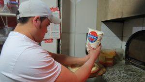 pizzaiolo prepara pizza na Pizza Estrela da Granja, usando Catupiry original