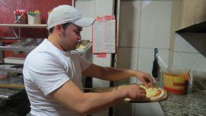 pizzaiolo prepara pizza na Pizza Estrela da Granja