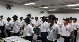 grupo de meninas em pé fazendo referência numa sala de aula