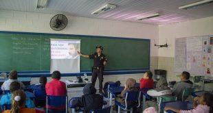 guarda civil de cotia dando palestra a crianças em sala de aula