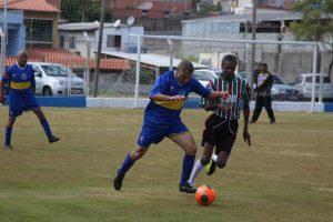 dois times masculinos disputando uma partida de futebol em Carapicuíba