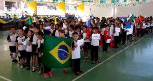 alunos da escola municipal Nai Molina, de Carapicuíba, desfilam em quadrapoliesportiva, divididos em grupos que representam os países participantes da Copa do Mundo