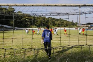 partida de futebol vista de trás de um dos gols