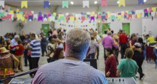 um tecladista visto de costas com o público à sua frente, em segundo plano, durante baile junino no Espaço Movimenta Cotia