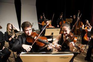 Alunos do Projeto Guri tocando violino, violoncelo e diante de partituras