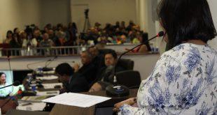 vereadora Nanda Costa discursa durante sessão na câmara de Carapicuíba, com outros vereadores no segundo plano e o público ao fundo