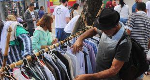 homem vasculha roupas penduradas em arara durante The Street Store em Carapicuíba