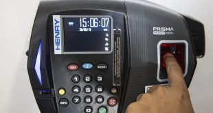 close da mão esquerda de uma pessoa com o dedo indicador pousado sobre a tela de leitura de impressão digital de um equipamento de controle biométrico