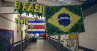 um corredor de uma escola pública de Cotia com bandeiras das nações participantes penduradas e seus respectivos nomes ao lado. A bandeira do Brasil aparece em primeiro plano, à direita, coom a bandeira da Costa Rica atrás, à esquerda, e parte da bandeira de Portugal