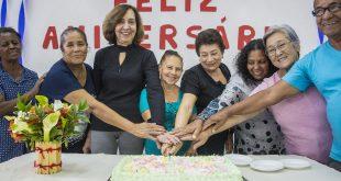 vários aniversariantes do mês partem um mesmo pedaço de bolo enquanto sorriem para a câmera