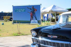 foto parcial da parte da frente de um carro dos anos 50/60 com um outdoor ao fundo com a imagem de um garoto e seu pai logo atrás com uma capa de superherói e os dizeres 'um dia de lazer para o seu super-herói'