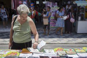 idosa folheando livrona feira do livro de cotia