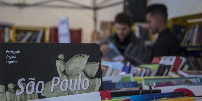 vários livros em primeiro plano, com algumas pessoas folheando-os em segundo plano