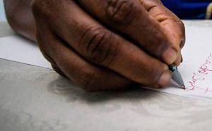 close de uma mão escrevendo algo