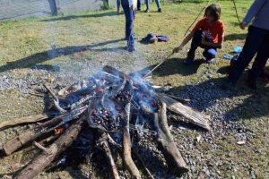 uma criança queimando pinh]pinhão em uma fogueira