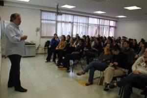 Georges Schnyder profere palestra a dezenas de pessoas em um auditório