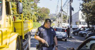 guarda civil de cotia observa carros passando por ele com uma arma em punho