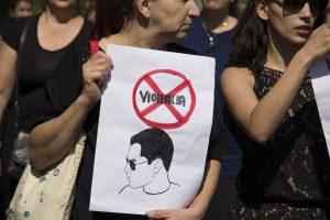 manifestantes segurando cartaz com a palavra violência riscada duas vezes e o desenho de um homem embaixo