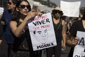 manifestantes segurando cartaz com o desenho de um homem e os dizeres 'Merecemos Viver sem medo de morrer'