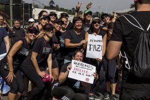 manifestantes sorriem para uma câmera com cartazes escrito 'queremos paz' e 'queremos de volta nosso direito de ir e vir'