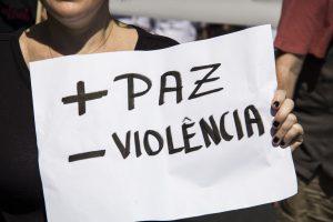 manifestante segurando cartaz escrito '+paz -violência'