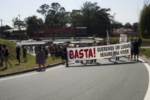 manifestantes caminham com faixa com os dizeres 'Basta! Queremos um lugar seguro pra viver'