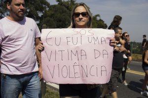 manifestante no viaduto william ortiz exibe faixa escrito 'sos eu fui uma vítima da violência'