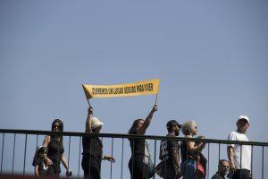 manifestantes caminham pelo viaduto william ortiz com uma faixa escrito 'queremos um lugar seguro para viver'