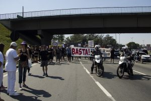 manifestantes caminham sob o viaduto william ortiz